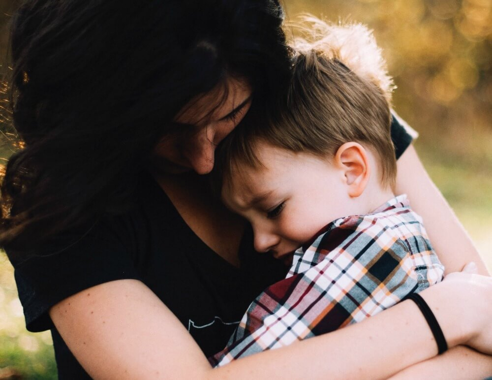 mom holding sad child